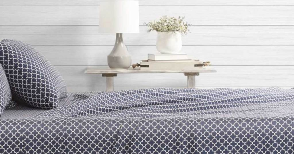 patterened sheet set on a bed in a room