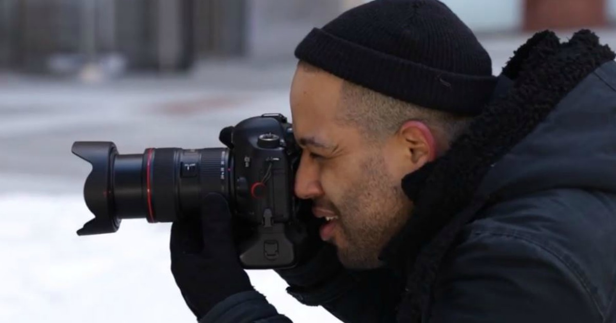 man with camera focusing on object