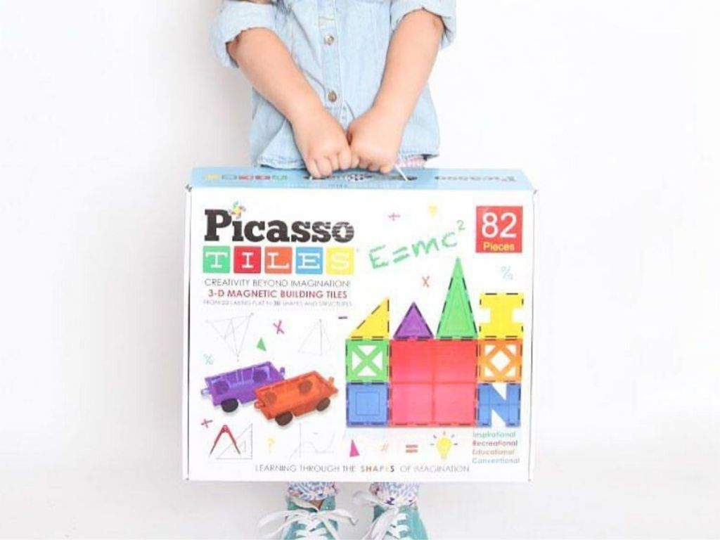 little girl carrying box with 82-count picassotiles building set
