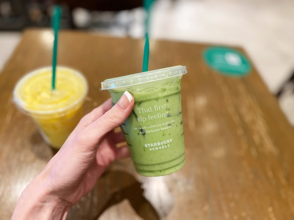 hand holding green cold drink at Starbucks
