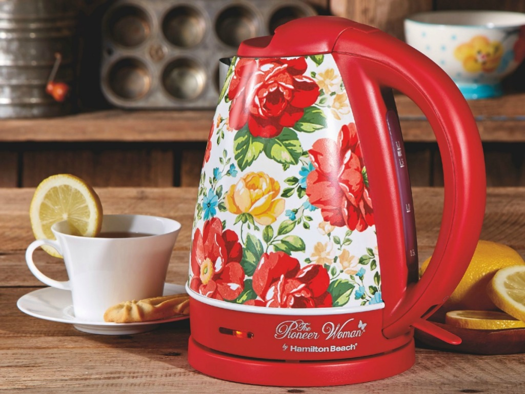 kettle in vibrant red color on counter by tea cup and lemons