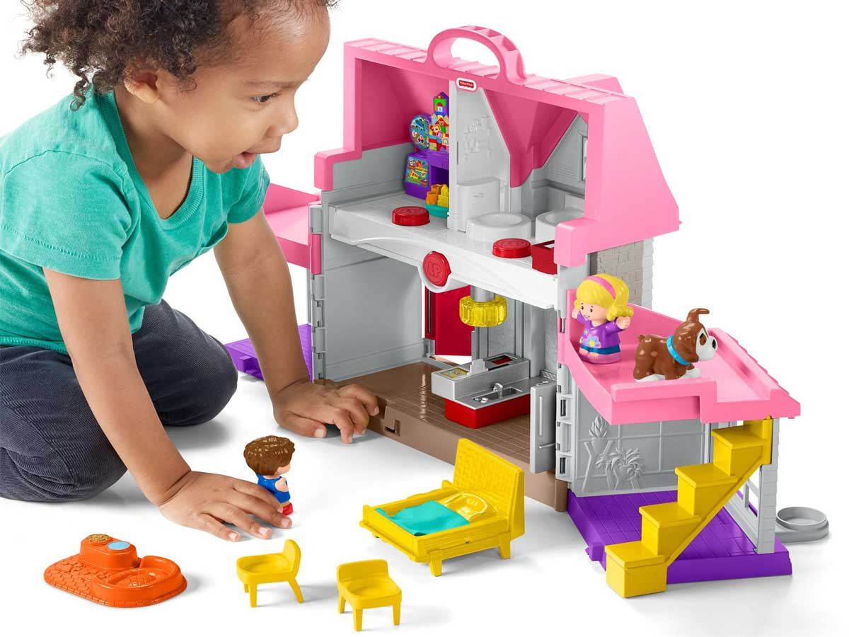 little girl playing with a fisher price play house
