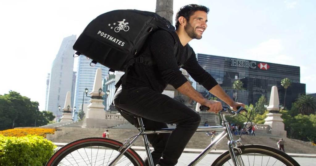 Man wearing Postmates backpack with bike