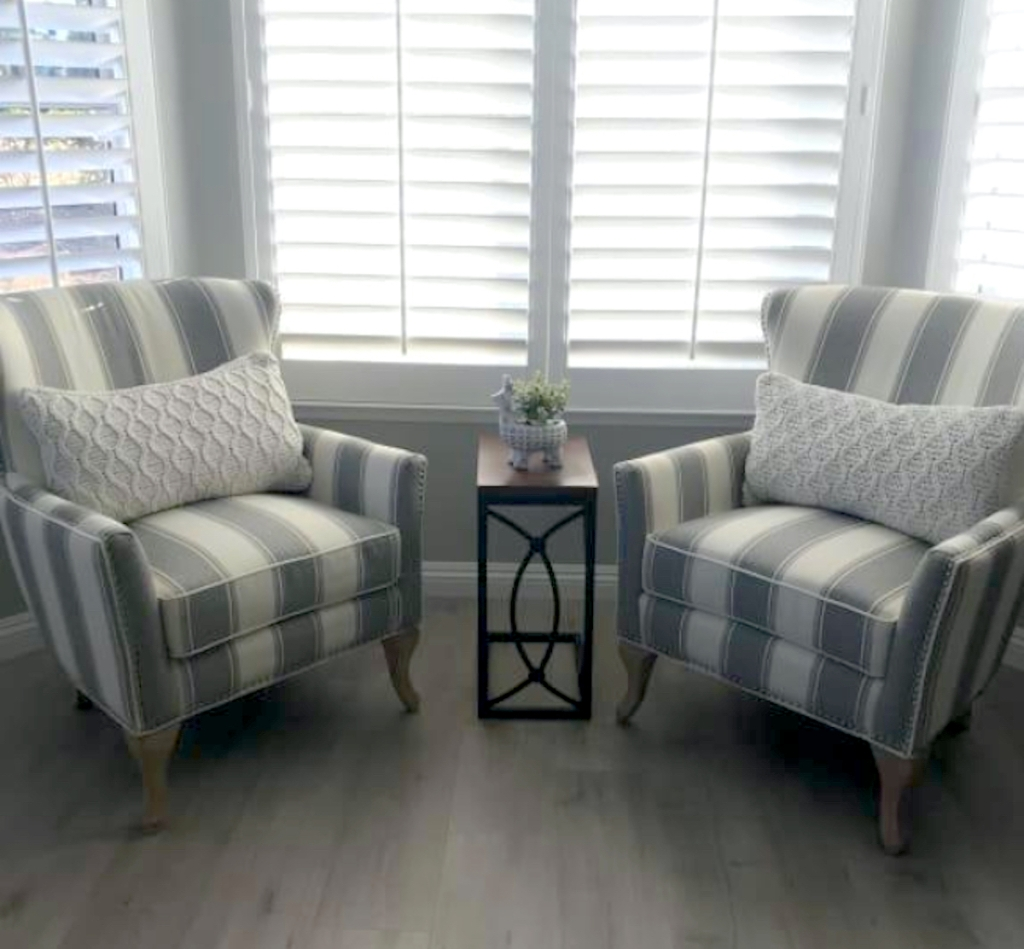 two stripe accent chairs sitting on wood floor in front of window with two white pillows