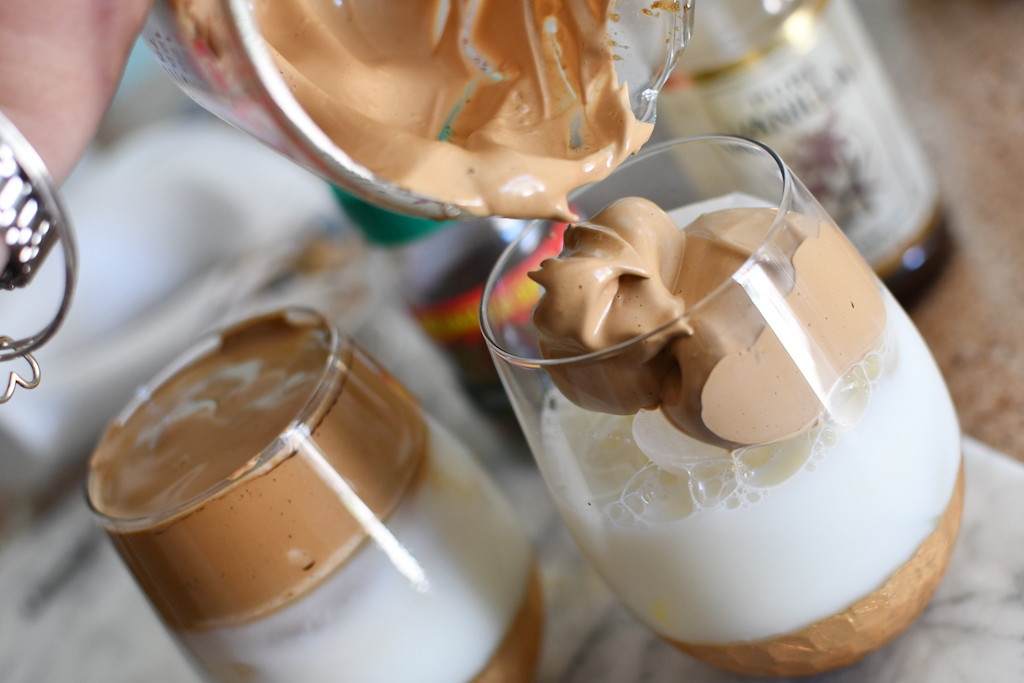 pouring whipped coffee in glass cup