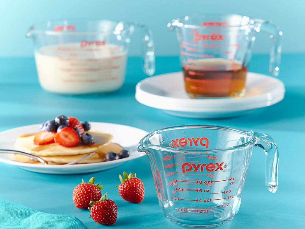 blue background with measuring cups, pancakes and strawberries