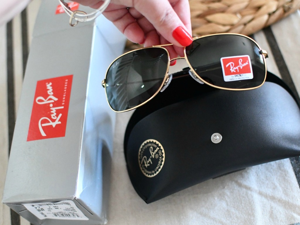 hand holding sunglasses by case and box on table