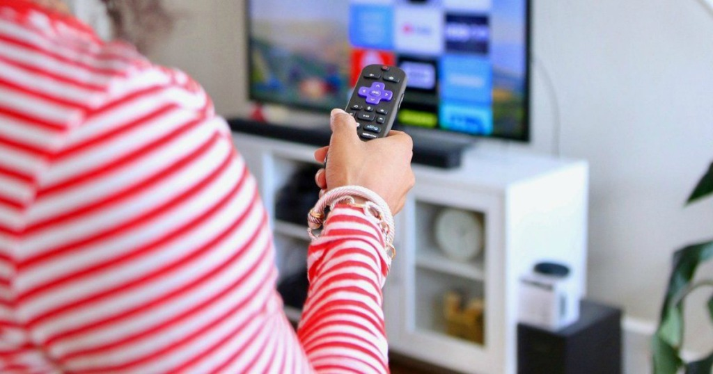 person holding roku remote