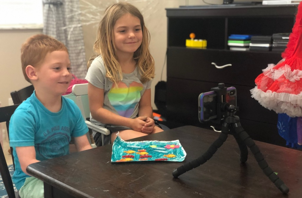 two kids sitting in front of phone on tripod smiling