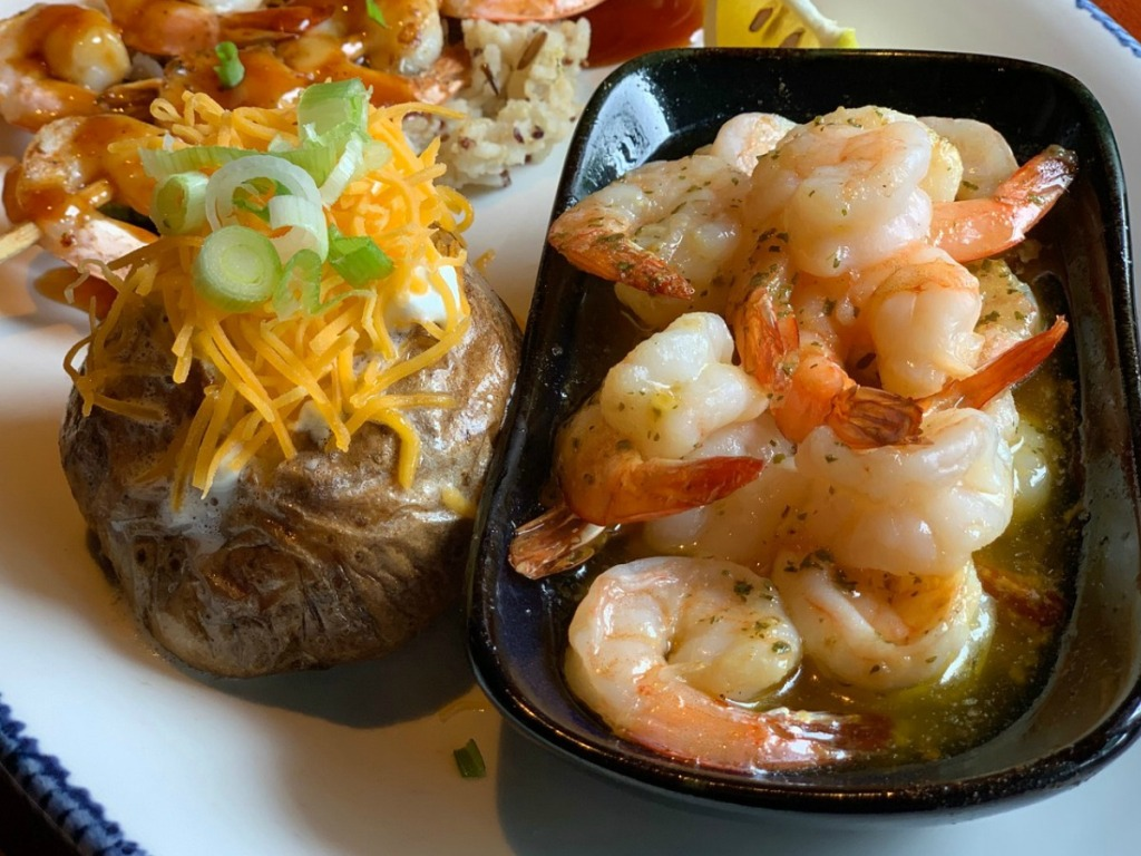 plate with baked potatoe and shrimp on it