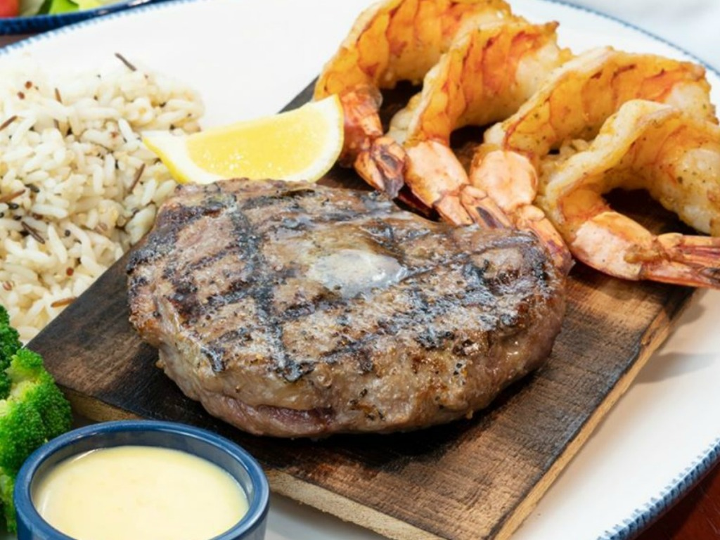 steak on plate with shrimp, dipping sauce and rice