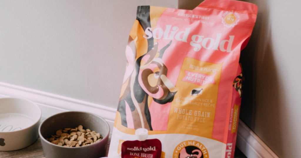 bag of solid gold dog food with dog bowls beside it