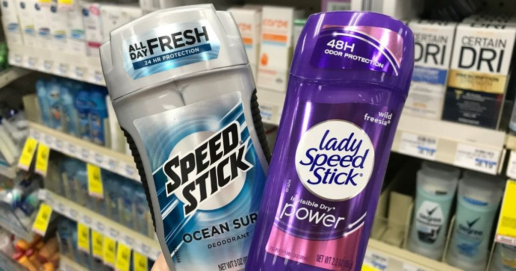 womans hand holding men's and woman's deodorant at the store
