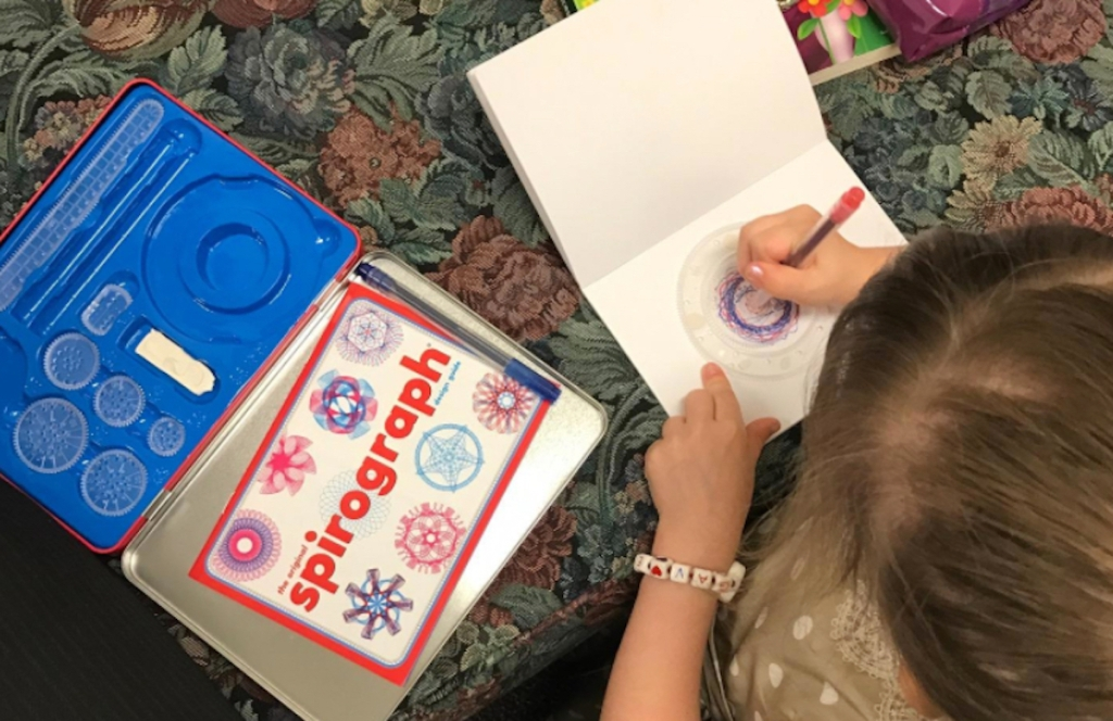 girl coloring on white paper with spirograph kit on table