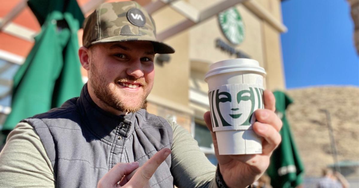 man holding hot starbucks drink outside