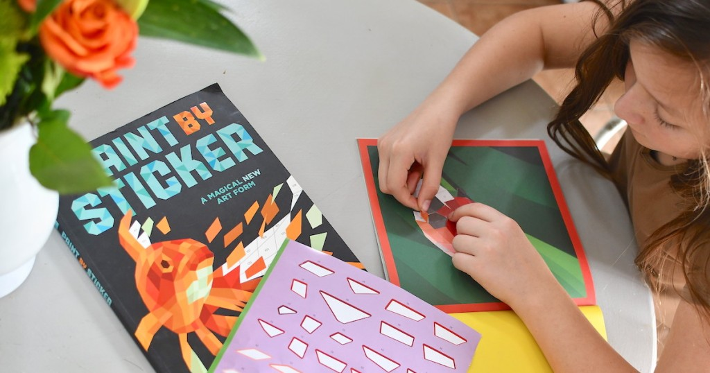 girl sitting at table putting geometric stickers on picture