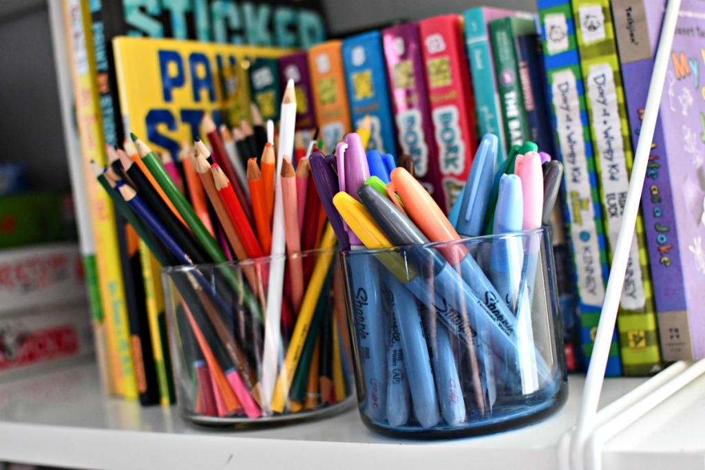 storing markers and pencils in candle jars