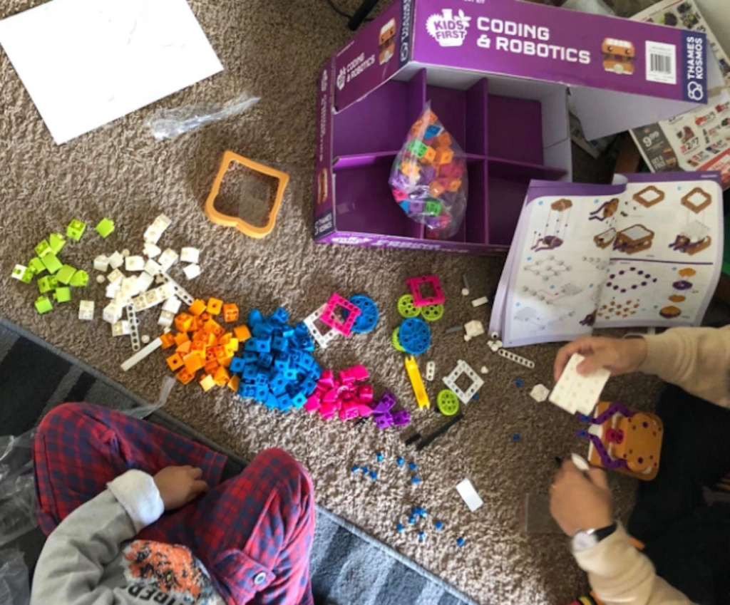 opening purple box full of colorful toy pieces to game
