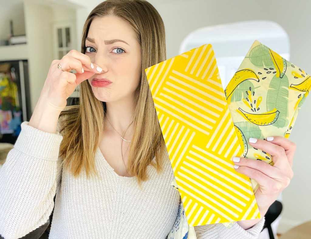 woman with fingers pinching nose while holding bright yellow wax bags