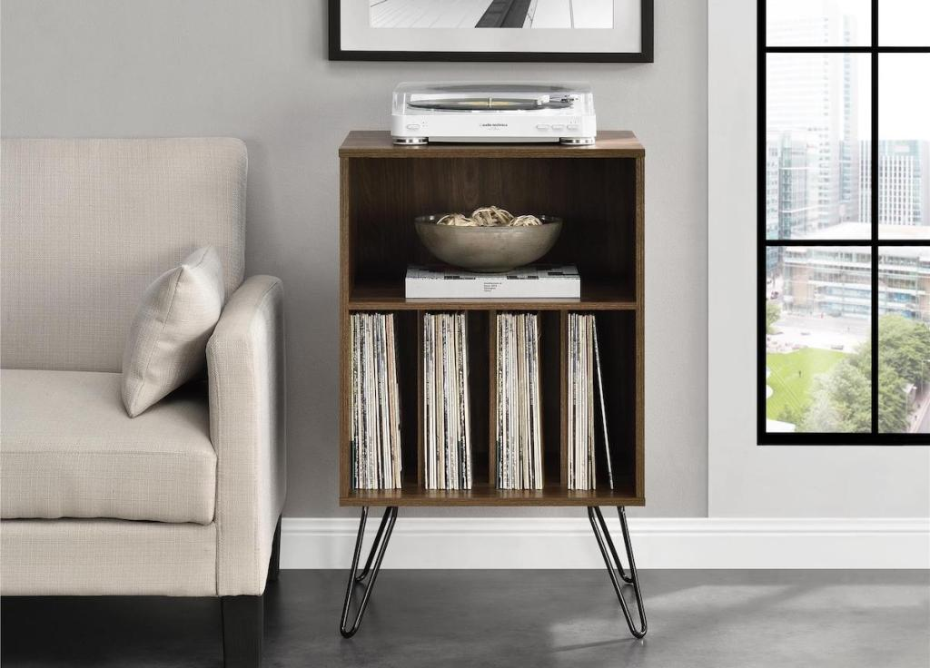 wood cabinet table with turntable on top and vinyl records on the bottom shelves