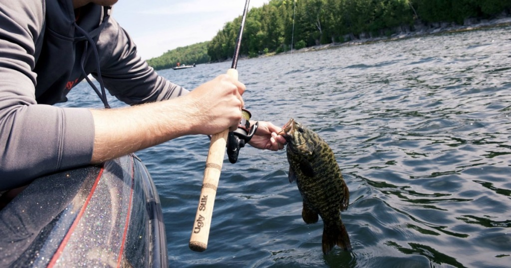 man holding fishing rod on water with fish