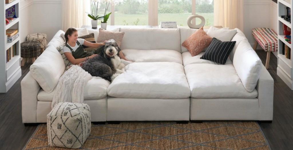 girl and dog sitting on huge white sectional sofa