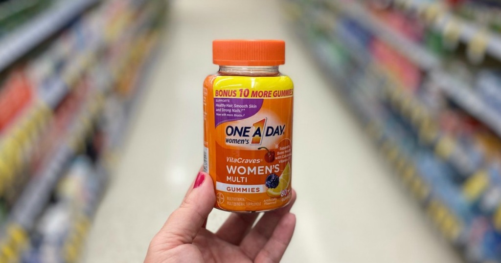 hand holding women's vitamins in a store
