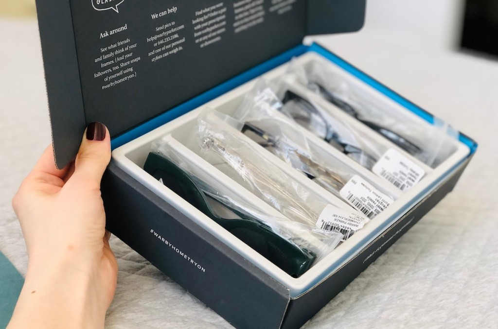hand holding a box full of sample eyeglasses and sunglasses