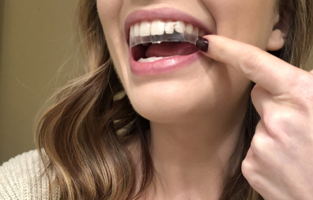 woman wearing whitening strip on teeth