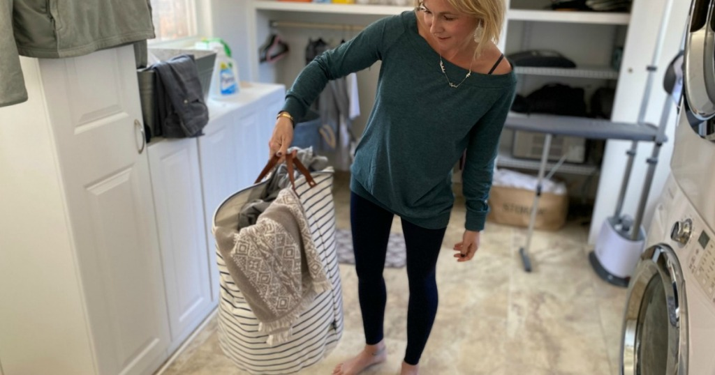 woman holding laundry hamper by washer/dryer