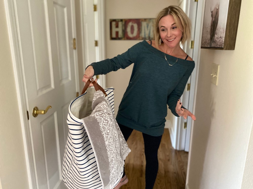 woman holding laundry basket with towel inside