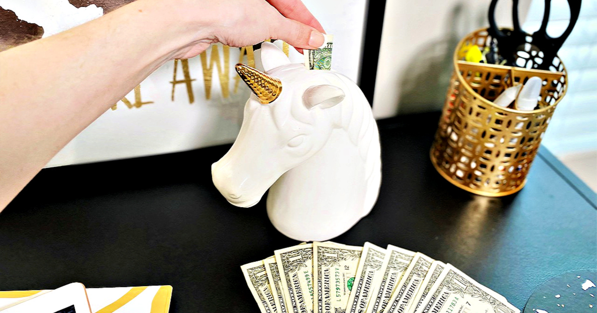 woman putting dollar bills in unicorn piggy bank for Christmas budget