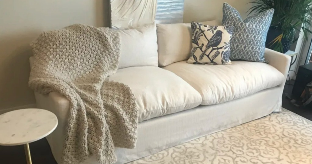 cream sofa with blanket and throw pillows