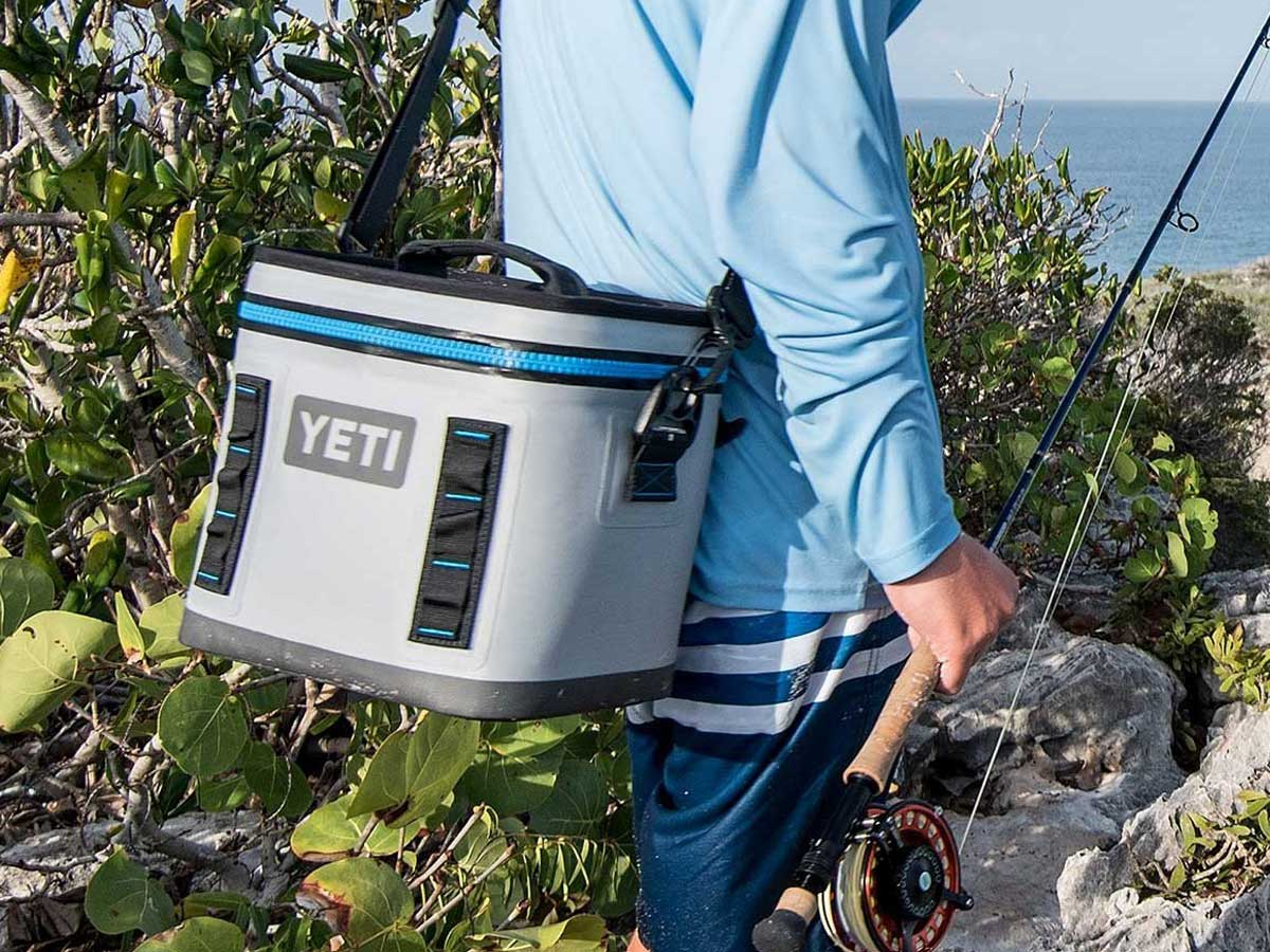 yeti flip 8 cooler on man's back by ocean