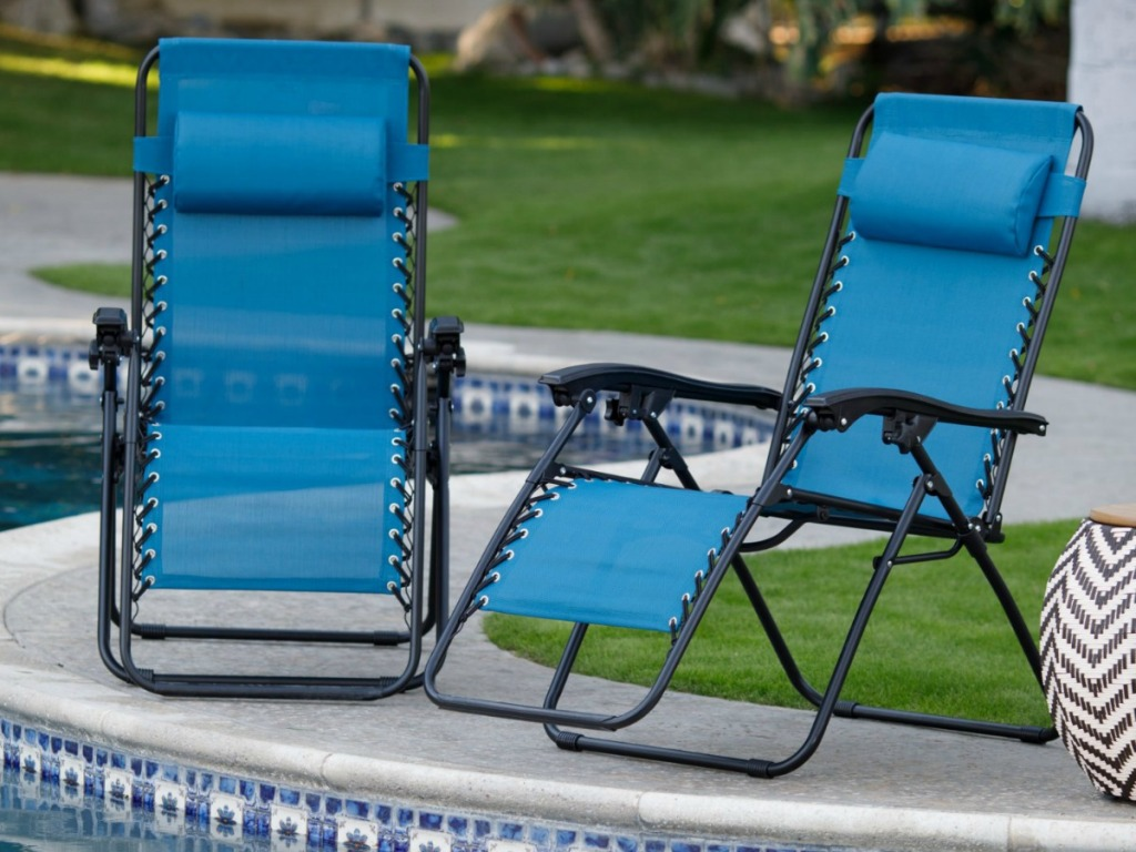 two blue recliner chairs sitting outside by pool