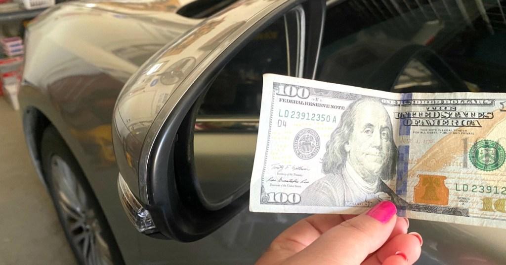 100 dollar bill next to a car