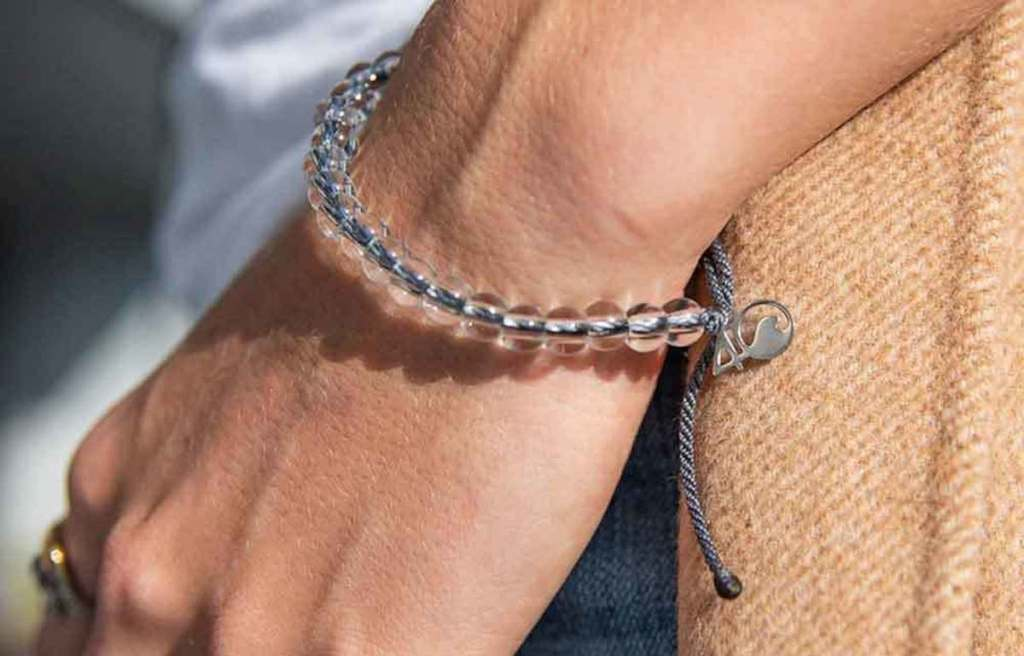 close up of persons hand wearing a gray and plastic bubble bracelet on wrist
