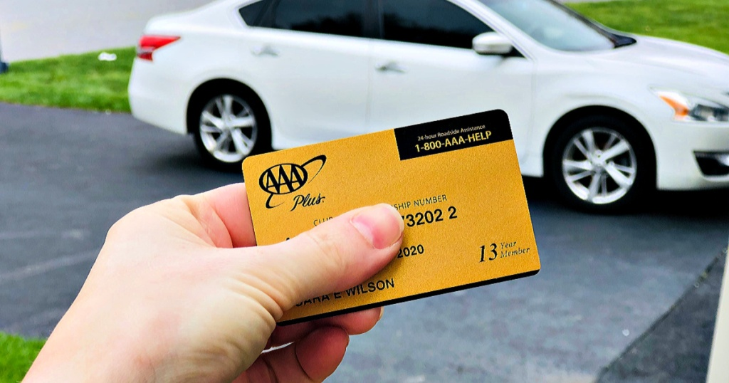 AAA Gold Membership in person's hand in front of white car