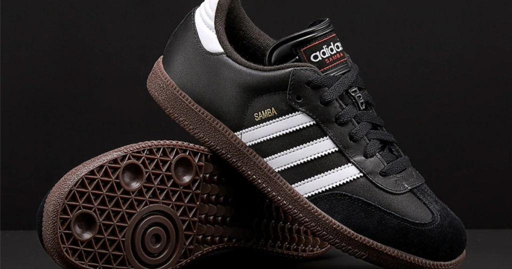 kids black Adidas soccer shoes and black background