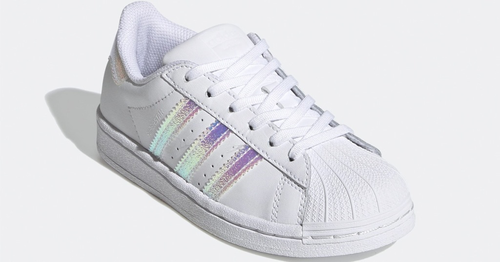 white adidas shoe with three lines of metallic foil on outside of shoe