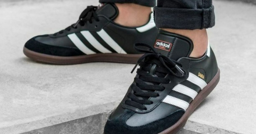 man wearing black Adidas soccer shoes on concrete outside