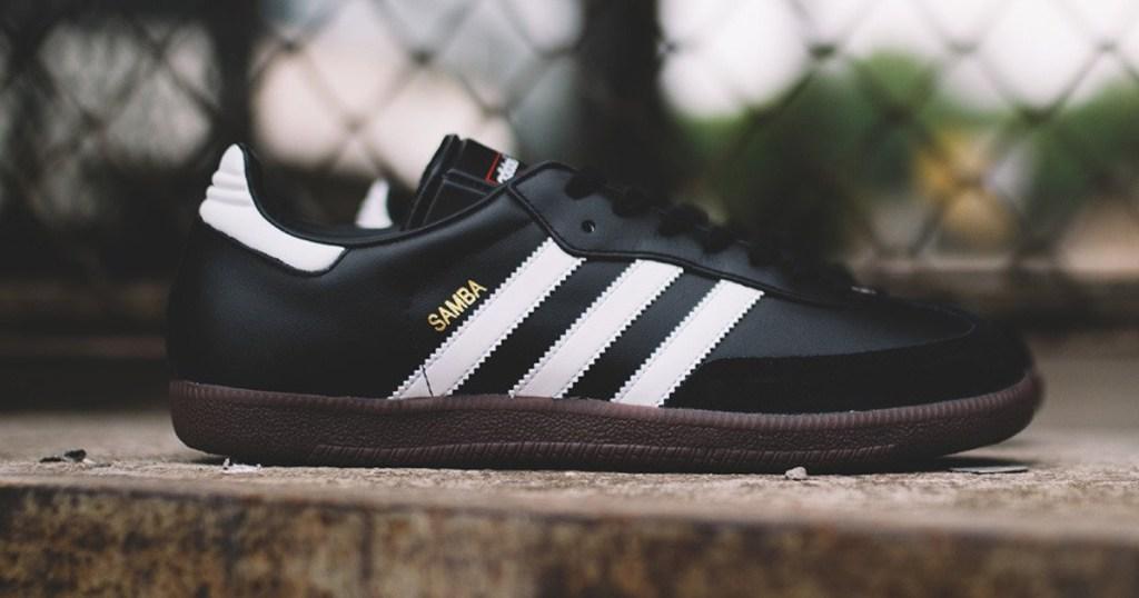 black Adidas soccer shoes on ledge outside