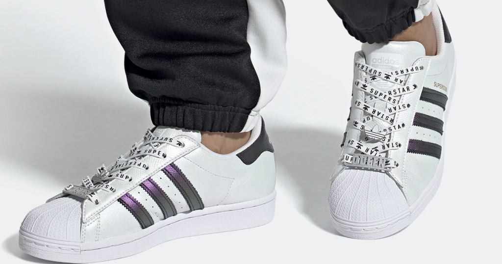 person wearing a pair of adidas white sneakers with 3 metallic purple stripes