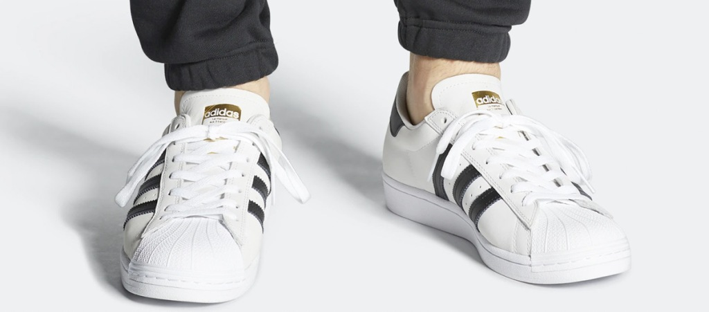 person wearing pair of white adidas shoes with three black lines on each side of shoe