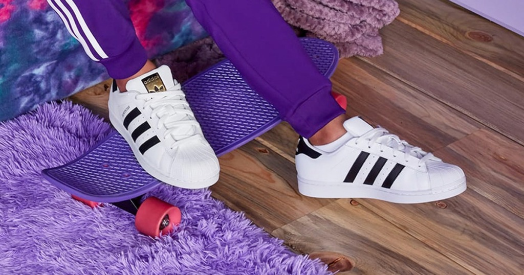 person wearing pair of white adidas shoes inside a room with a purple shag rug and purple skateboard