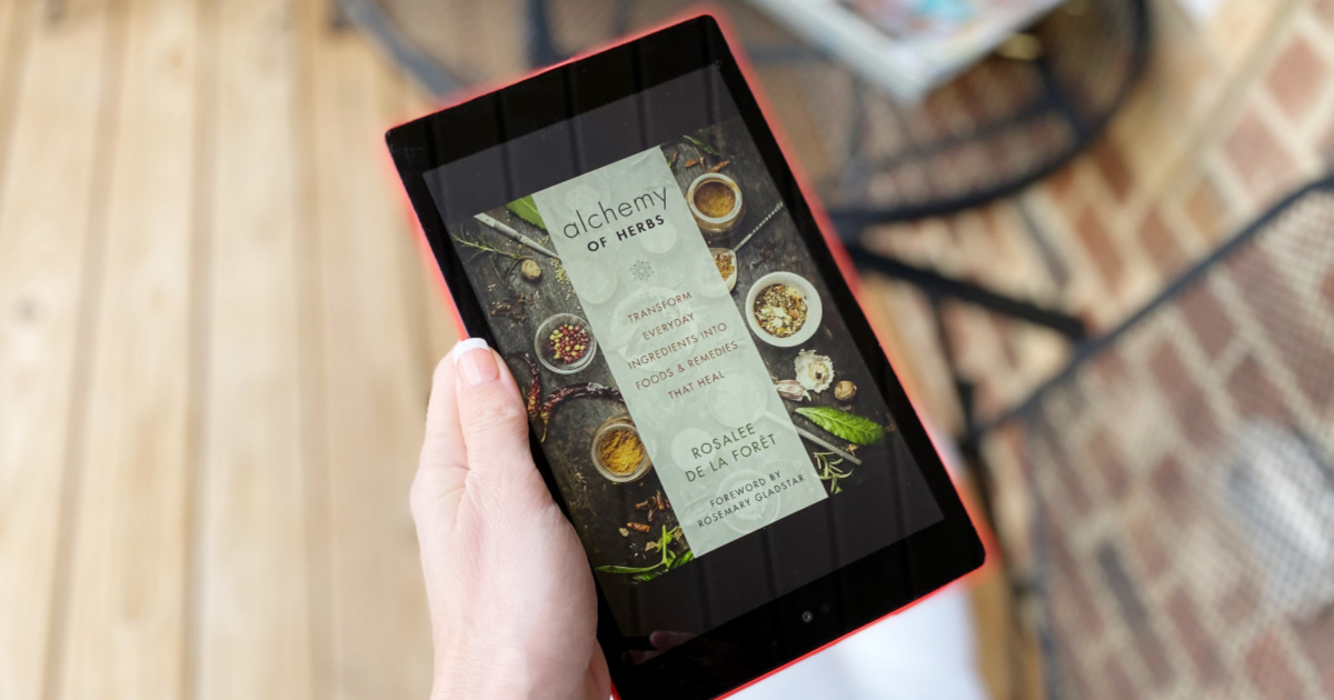 woman hand holding kindle with alchemy of herbs book