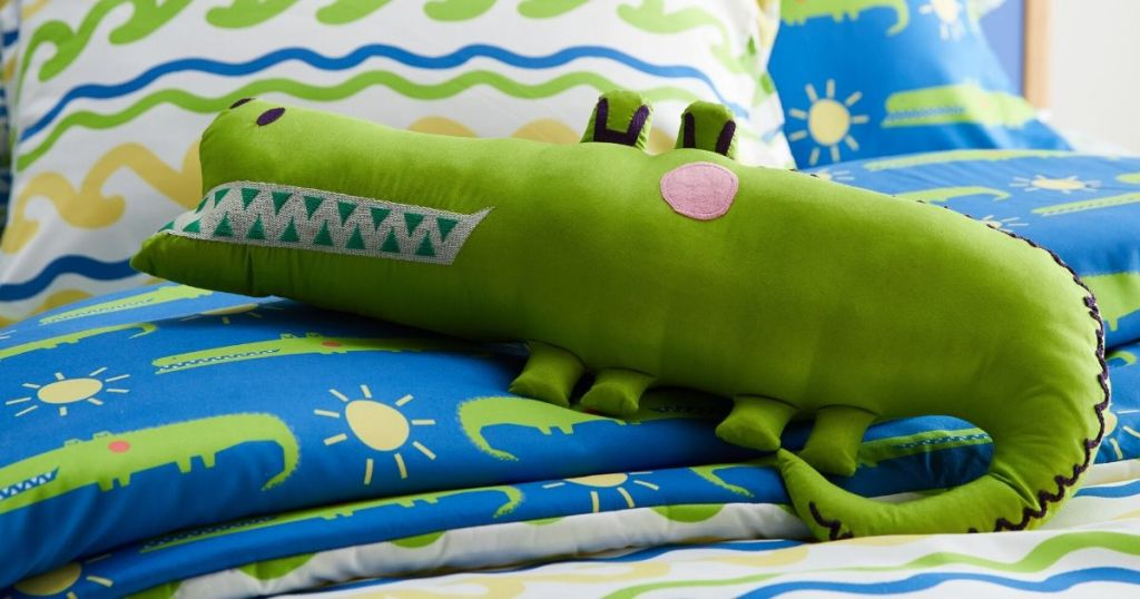 Stuffed alligator shaped pillow on bed