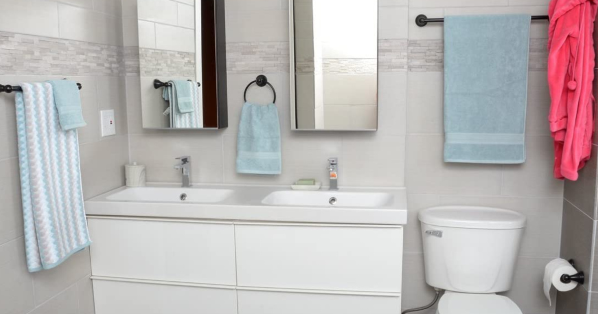 white bathroom with blue towels on dark bronze towel bar set
