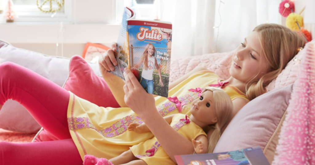 girl laying in bed with american girl doll reading american girl book