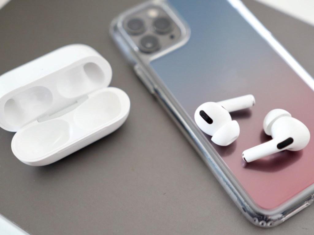 earbud tanpa kabel putih di ponsel dan casing pengisi daya di atas meja